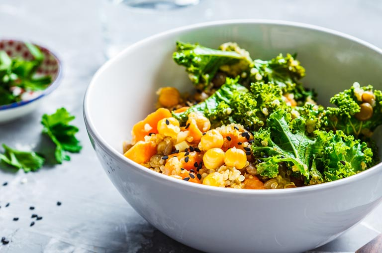 Kale, corn, and a grain in a white bowl